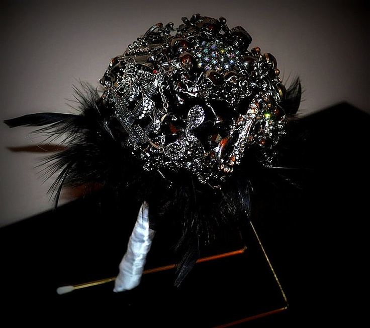 a fantastic black brooch wedding bouquet with feathers is a bold statement for a Halloween bride