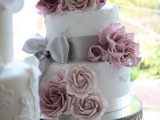 a romantic lace wedding cake with mauve and blush blooms and grey ribbons and a bow