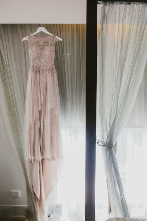 a gorgeous mauve wedding dress with a lace embellished bodice, no sleeves and a layered skirt