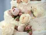 a textural white wedding cake with ivory and mauve blooms for decor is a very chic idea
