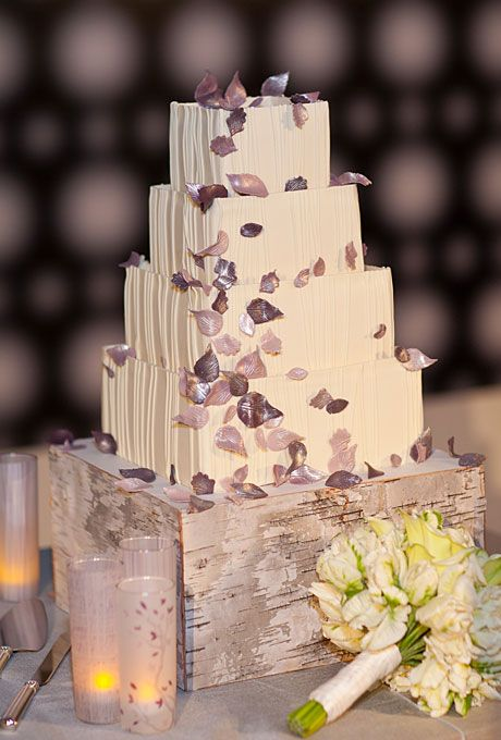 a white textural wedding cake with mauve and purple petals served on a birch bark box