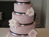 a large mauve wedding cake with white sugar blooms and ribbons is a stylish and tender wedding idea