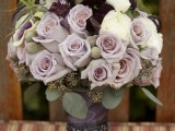 a wedding bouquet with mauve, dark, white, deep purple blooms, greenery and air plants
