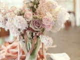 a tender wedding centerpiece with white, blush and mauve blooms and some ribbons