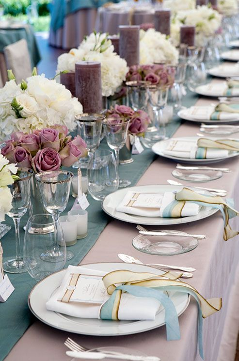 an elegant blue, mauve and blush wedding tablescape with mauve candles and roses that make it unusual
