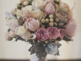 a delicate and soft wedding bouquet with mauve, ivory and blush blooms and berries