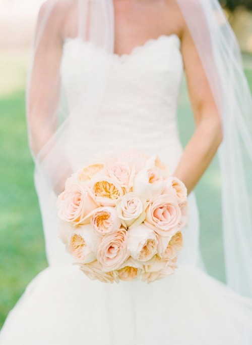 a pretty peachy and blush wedding bouquet of roses and peony roses is a stylish idea for a bride