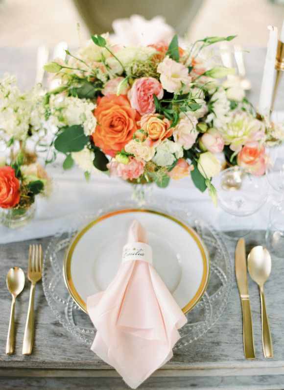 a peachy wedding tablescape with a white, coral and orange floral centerpiece, a blush napkin and gold cutlery is amazing
