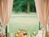 a romantic and elegant wedding tablescape with a peach, orange and white floral centerpiece, candles, blush candleholders and a blush napkin
