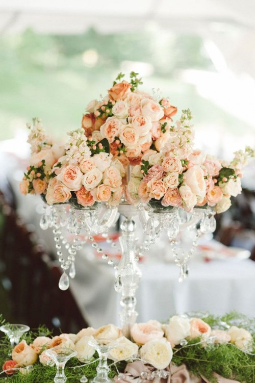 a refined wedding centerpiece of crystal, with blush and light pink blooms, berries and greenery is a very exquisite idea