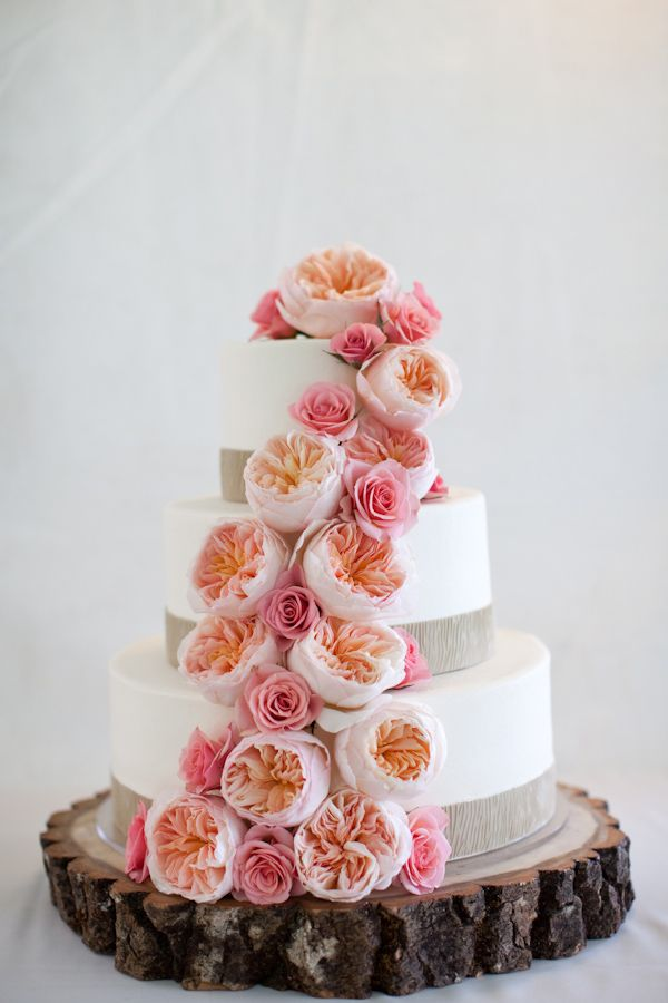 a white wedding cake with a burlap ribbon and with pink and peachy peony roses looks beautiful and chic