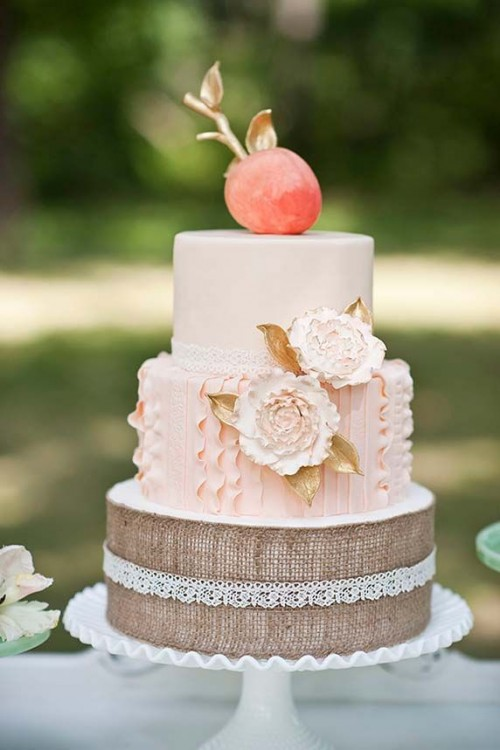 a beautiful wedding cake with a burlap tier, a peachy one, a neutral tier and a sugar peach with gold leaves on top