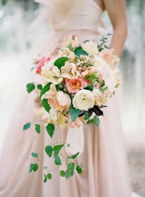 a beautiful peach and cream wedding bouquet with lovely blooms and greenery plus hanging down greenery