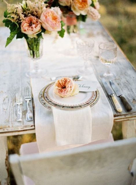 a chic wedding tablescape with neutral linens, printed plates, peachy blooms and greenery and refined cutlery