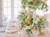 a beautiful peach and cream wedding tablescape with blush glasses, peachy, blush and white blooms and greenery decorating the table in a lush way