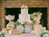 a pretty peach and cream sweets table with peachy and orange blooms and greenery, peachy sweets and candleholders