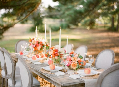 a beautiful peach and cream wedding tablescape with peachy and orange blooms, greenery, elegant candles and peaches marking each place setting