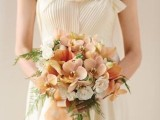 a delicate peach and cream wedding bouquet with peachy and rust blooms plus greenery and peachy ribbons is very elegant