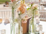 a vintage cream and peach wedding centerpiece of vintage books, peachy and pink blooms and white wildflowers is cool and chic