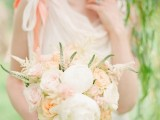 a very delicate peach and cream wedding bouquet with just some greenery looks subtle and chic