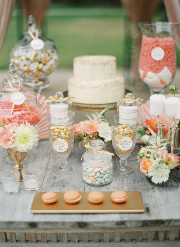 a lovely peach and cream sweets table with coral candies in jars, peachy macarons, peachy and coral blooms and greenery and leaves