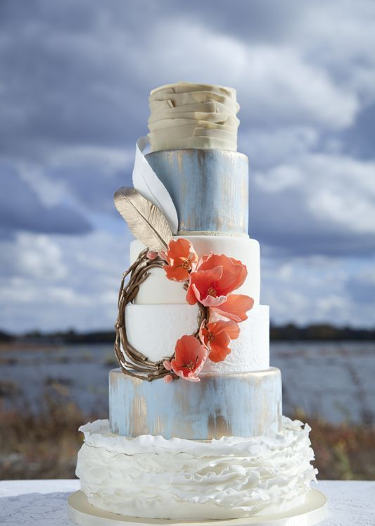 a bright boho chic wedding cake with white, blue and metallic tiers, with a wreath with sugar flowers and feathers