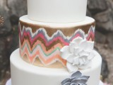 a white and copper wedding cake with a colorful printed tier, gold glitter ribbons and sugar blooms