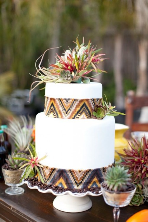 a white wedding cake decorated with ethnic print ribbons and bright succulents and air plants on top