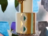 a bright wedding cake with colorful stripes, gold leaf and ethnic patterns plus sugar flowers on top