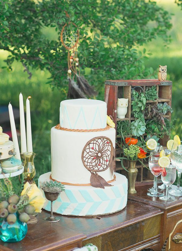a white and striped wedding cake in mint, white and with a chocolate dream catcher for decor