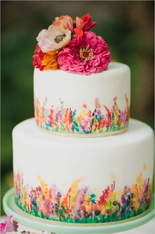 a colorful floral wedding cake with bright frehs blooms on top for a flower child wedding