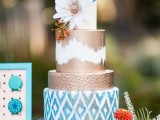a bright wedding cake with a navy, blue printed, copper and copper and white wedding cake with blooms and colorful feathers for a free-spirited wedding