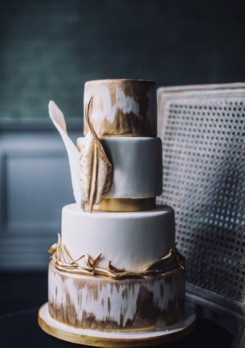 a whimsical gold and white wedding cake with an ikat tier, large gold leaves for decor
