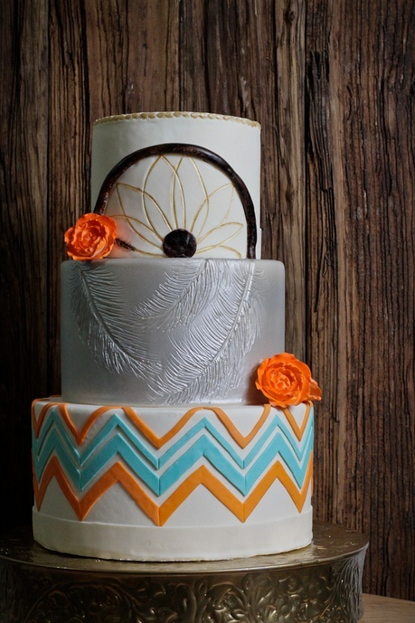 a colorful wedding cake with a bright geometric tier, a grey one and a dream catcher one with colorful blooms