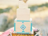 a white wedding cake with bright patterns on one tier and some sugar blooms on top for a boho feel