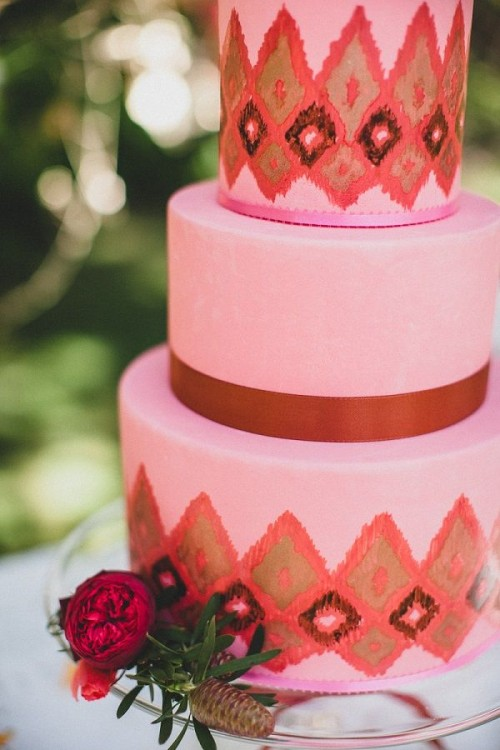 a pink wedding cake with burgundy ribbons and bright ikat patterns plus fresh blooms for detailing
