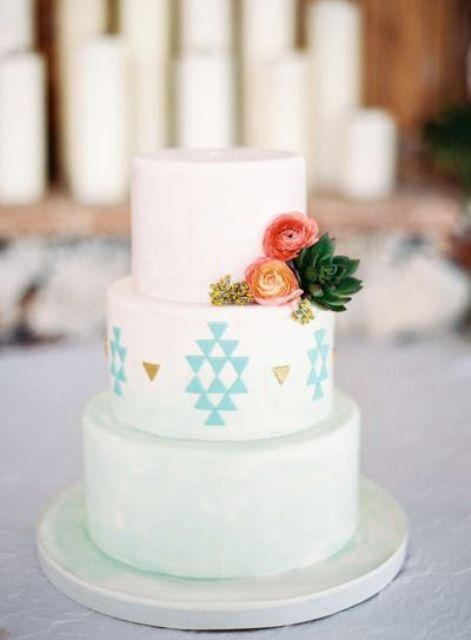 an ombre white to mint wedding cake with geometric patterns and gold leaf plus some fresh blooms and leaves