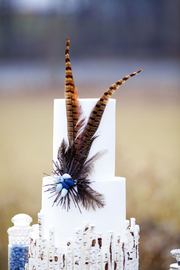 a white wedding cake with a birch branch tier and a lush decoration with sugar beads and feathers