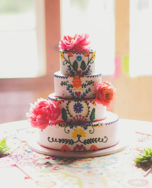 a colorful boho patterned wedding cake with ethnical motifs and bright fresh blooms for decor