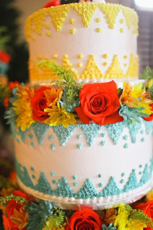 a bright yellow and green wedding cake with patterns and bright blooms and greenery for a colorful wedding