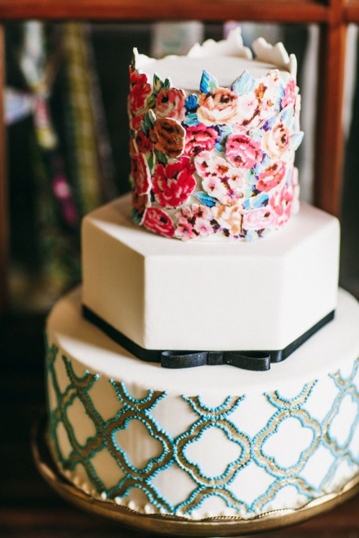 a bright wedding cake with a white geometric tier, a printed and a floral one for a whimsical wedding