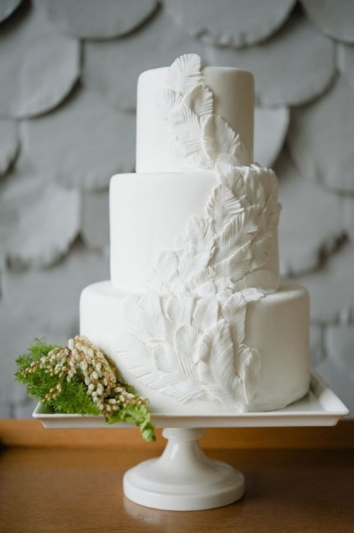 a pure white wedding cake with feather detailing is a unique boho idea done in neutrals