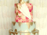 a bright mint and gold lead wedding cake with a colorful geometric tier and some gilded edge feathers