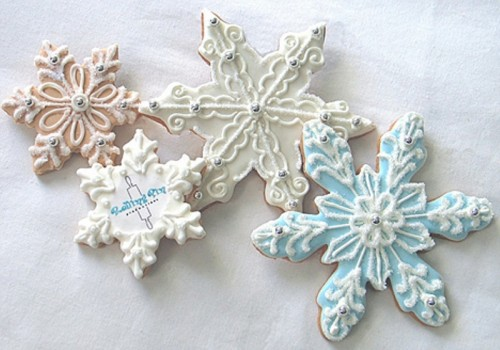 snowflake-shaped cookies with blue and white icing are amazing to embrace the season, they can also be nice wedding favors