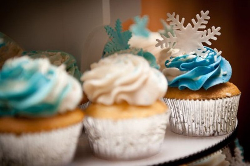 cupcakes with white and blue icing and snowflakes on top are amazing to give a wintry feel to your dessert table