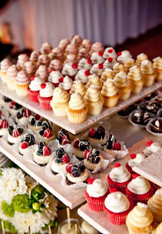 tasty cupcakes with whipped cream and fresh berries and mini cheesecakes with fresh blueberries, blackberries and raspberries