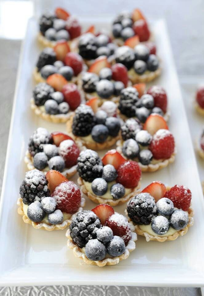 mini tartlets with custard and fresh bluberries, blackberries and raspberries on top and some sugar powder