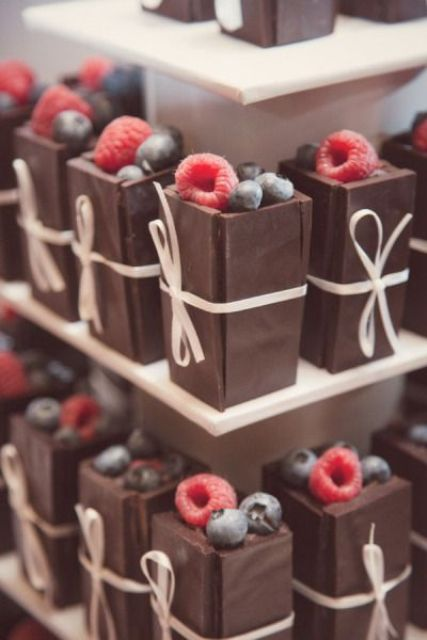 mini chocolate desserts filled with cream and fresh berries on top plus some ties and bows