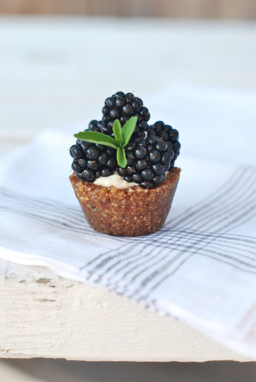 a mini tartlet filled with curstard and topped with blackberries is a delicious little dessert
