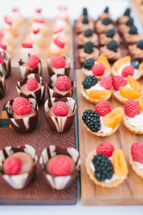 mini chocolate cups with chocolate cream and fresh raspberries on top and mini tartlets with whipped cream, fresh raspberries and blackberries plus fruit